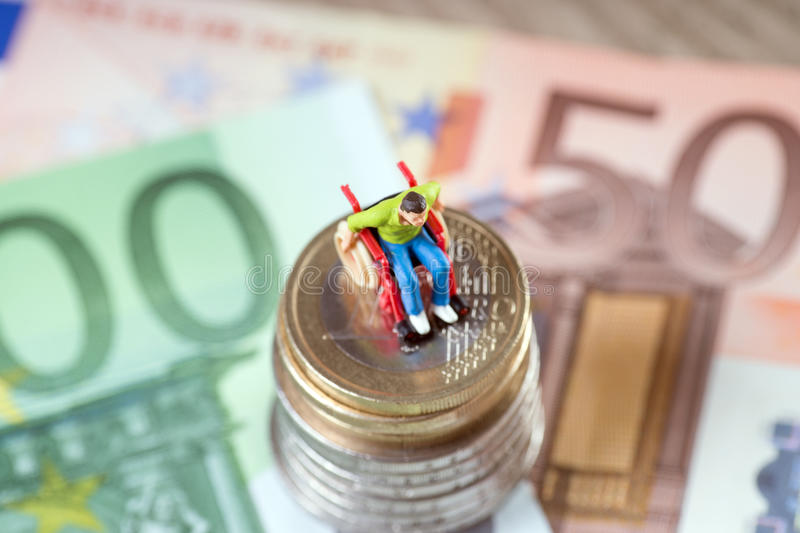 Wheelchair user. On a stack of euro coins with euro banknote stock image