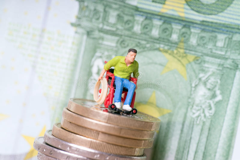 Wheelchair user. On a stack of euro coins with euro banknote royalty free stock images