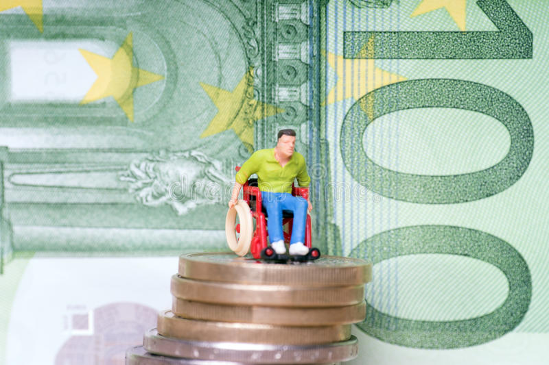 Wheelchair user. On a stack of euro coins with euro banknote royalty free stock image