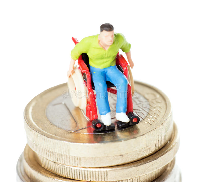Wheelchair user. On a stack of euro coins over a white background stock images