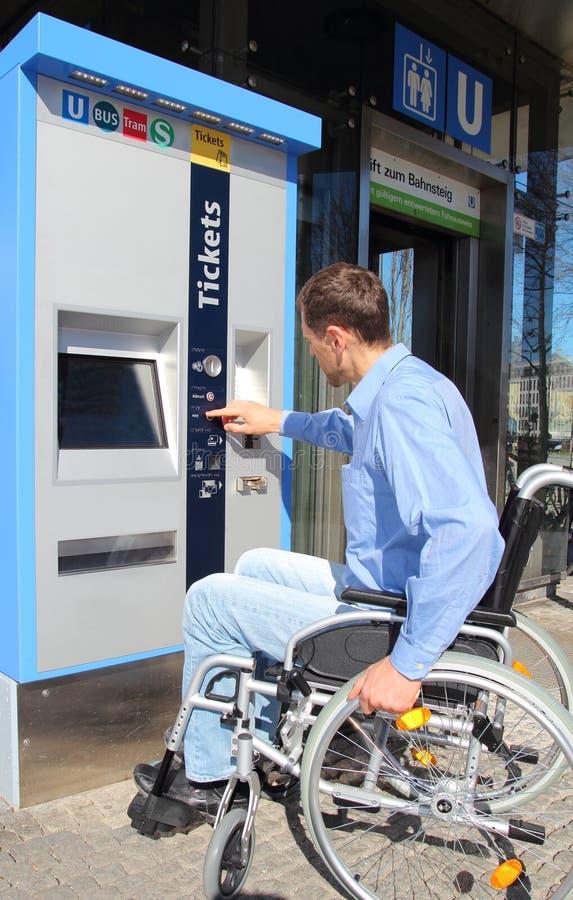 Wheelchair user on a ticket machine. A Wheelchair user on a ticket machine royalty free stock photo