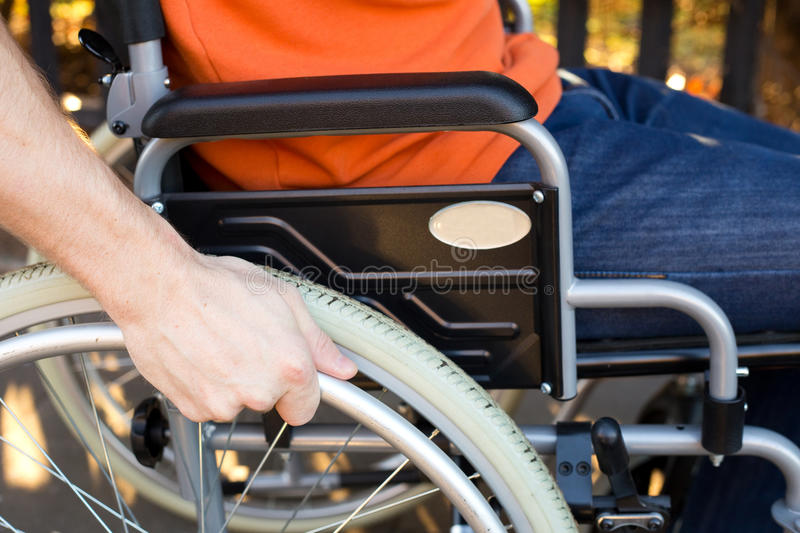 Wheelchair. A young wheelchair user with his hand on the wheel stock photos