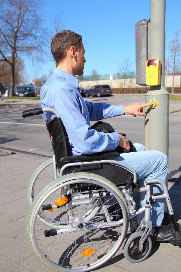 Wheelchairuser em um cruzamento pedestre fotografia de stock royalty free