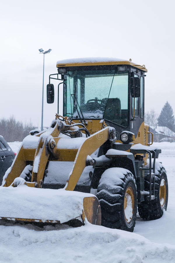 Wheeled snow plow tractor with a bucket. Yellow wheeled snow plow tractor with a bucket all covered with snow stands on the cleared the Parking lot after a heavy stock image
