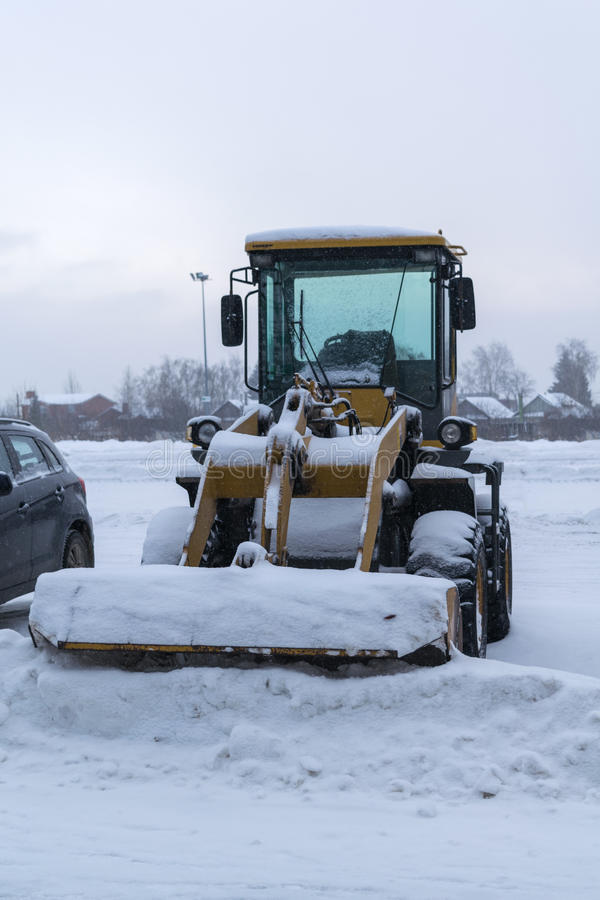 Wheeled snow plow tractor with a bucket. Yellow wheeled snow plow tractor with a bucket all covered with snow stands on the cleared the Parking lot after a heavy stock photography