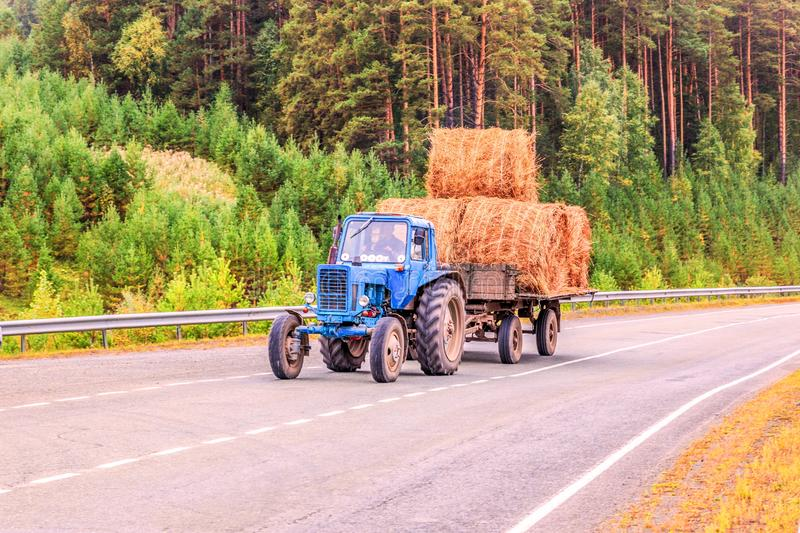 A wheeled tractor with a trailer with hay rides on the road. A wheeled tractor carries a cart with rolls of hay on the highway stock photography