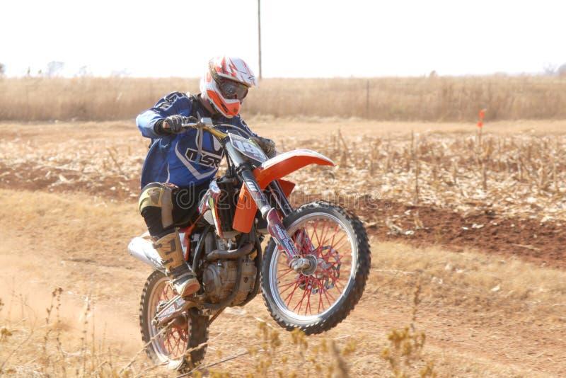 Wheelie мотоцилк на заднем колесе пиная вверх след пыли на песке стоковая фотография rf