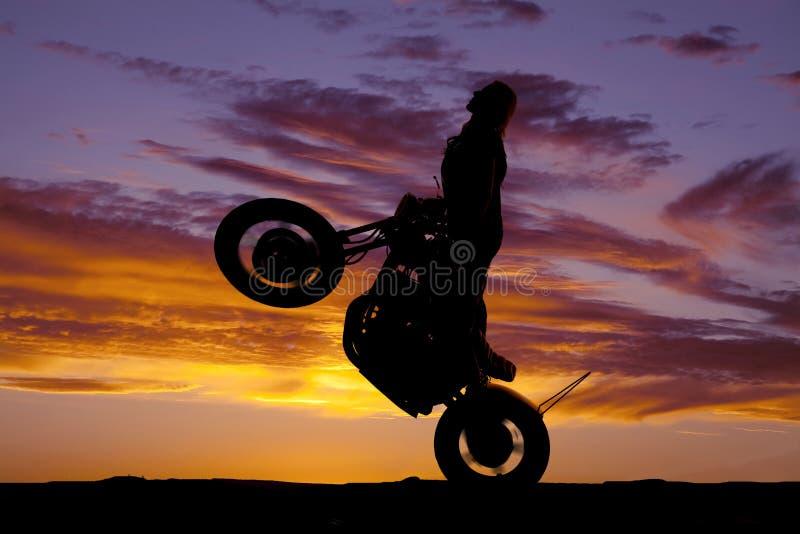 Wheelie de tour de moto de femme de silhouette photographie stock libre de droits