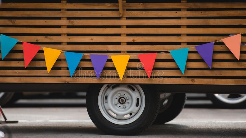 wheels and bottom part of food truck with colorful flags royalty free stock photo