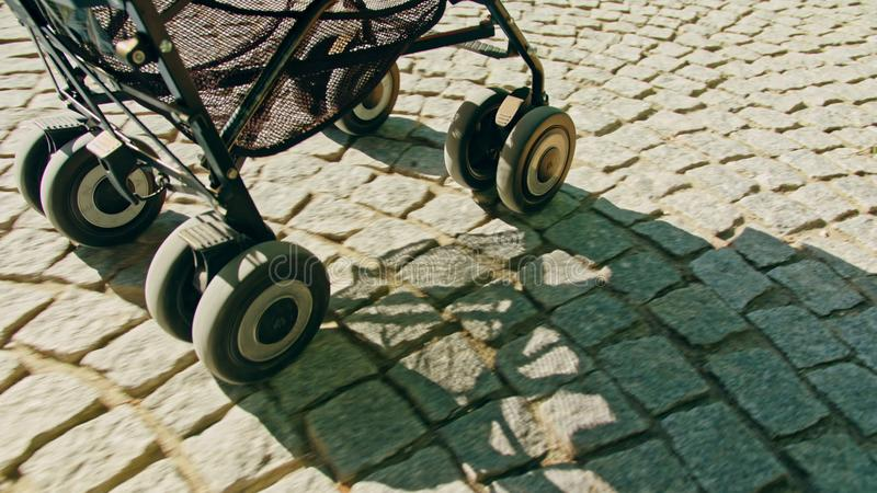 Wheels of a Stroller Rolling on Cobble Stone Road stock image