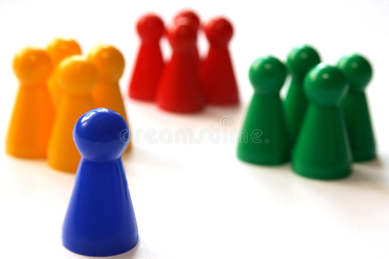 Where do I fit in. A blue game figurine in front of groups of figurines, symbolizing the concept of being new to a group, trying to integrate royalty free stock photo