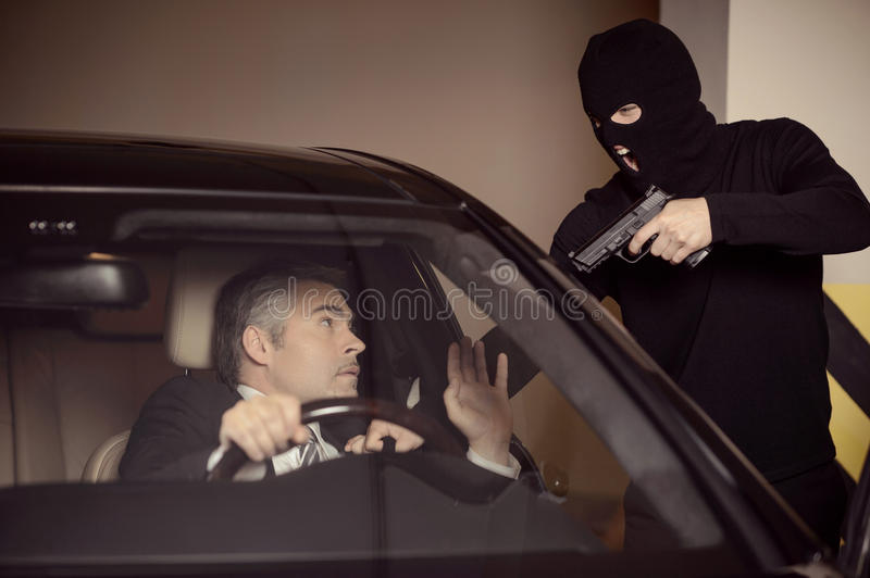 Where is the money?. Men in black balaclava holding gun and aiming a shocked mature businessman sitting on the front seat of a car stock photo
