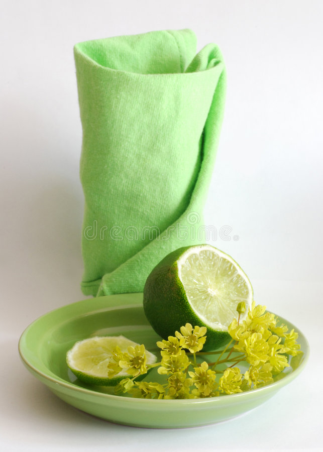 Where is tea?. Green napkin, lime and maple flowers on a saucer royalty free stock photography