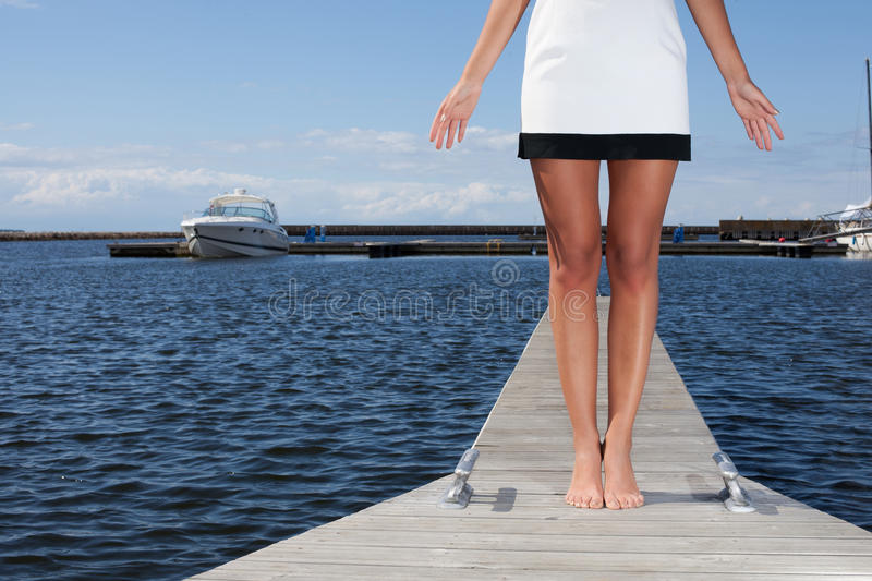 Where is your boat, sir?. Girl in mini near an empty dock asking: Where is your boat, sir royalty free stock images