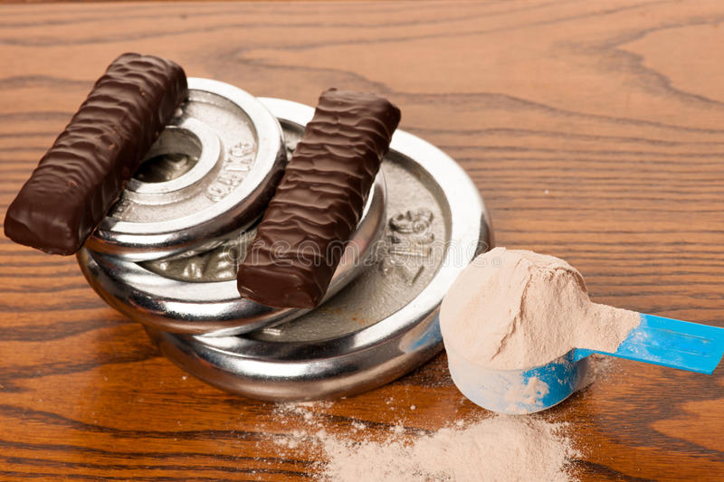 Whey protein powder in measuring scoop, protein bar, meter tape royalty free stock photos