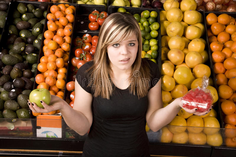 Which one. A teen girl trying to decide if she should eat candy or fruit stock images