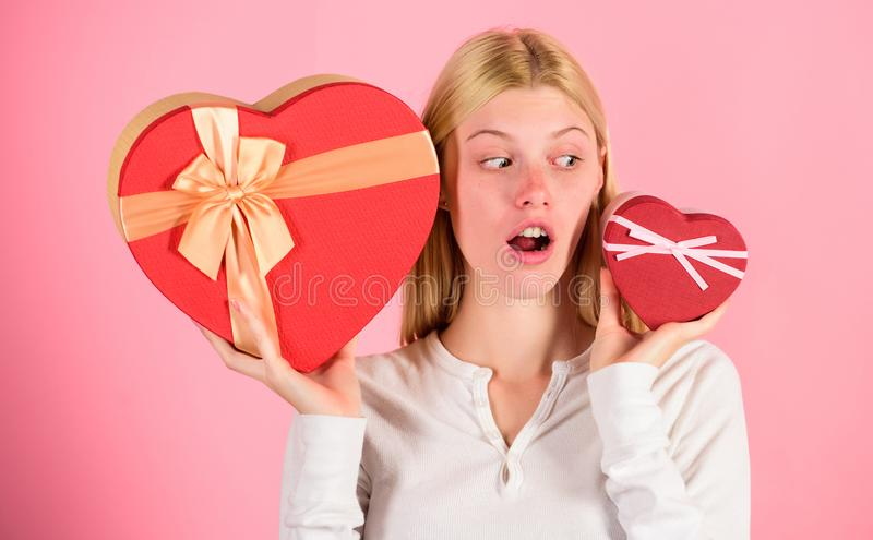 Which one she prefer. Girl decide which gift she like more. Big surprise and small gift. Make choice. Romantic gift for stock photography