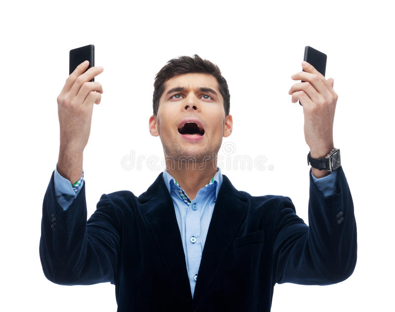 Which one to pick?. Businessman is in mess with phones royalty free stock photo