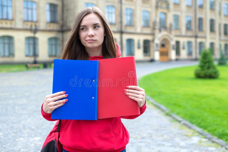 Which university I should apply to? Closeup photo of pensive having many thoughts teen deciding which college she what to apply to. Holding two folders with stock images