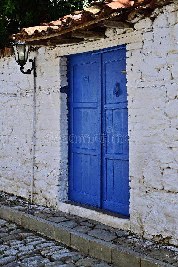 Blue door in Elbasan, Albania. Whie wall and blue door  creating mediterran mood in the medieval fortress of Elbasan, Albania. Elbasan has been occupied by royalty free stock photo