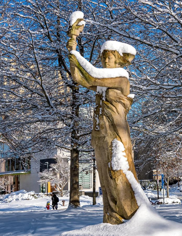 A sculpture of a woman holding a torch is shown on a wintry and clear day covered in snow royalty free stock images