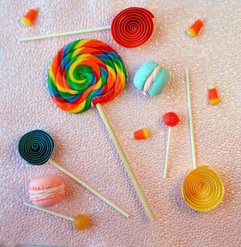 Lollipops macaroons and candy corns on pink background with paper lolly pops royalty free stock photos