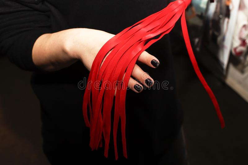Whip red, sex toy in female hands royalty free stock photo