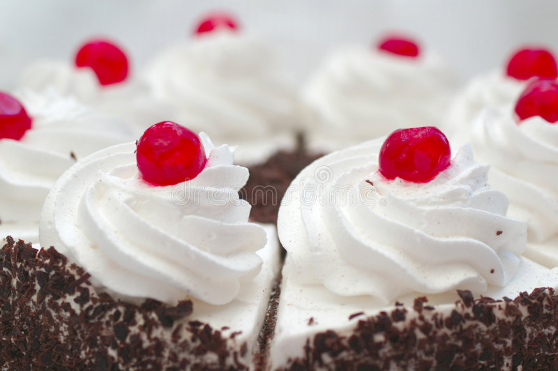 Whipped cream on the cake with a cocktail cherries royalty free stock image