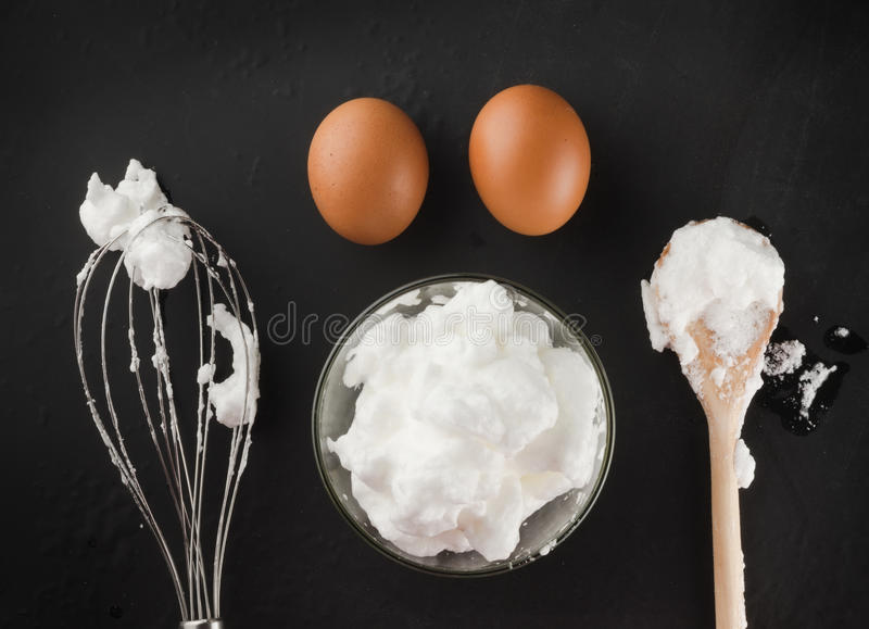 Whipped egg whites for cream in a glass bowl, whisk and wooden s royalty free stock photography