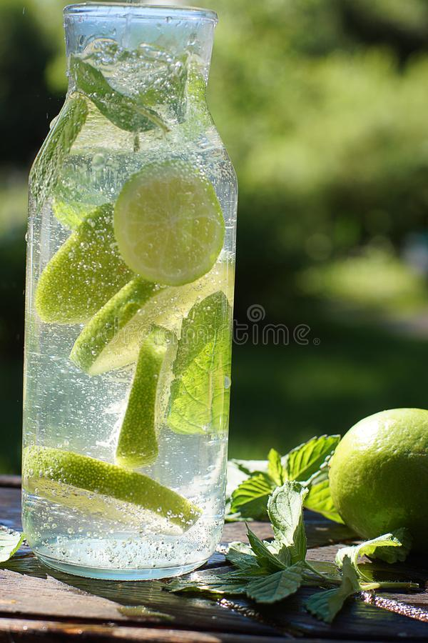A whirl of mint and lime in a bottle with homemade mojito cocktail.  royalty free stock images
