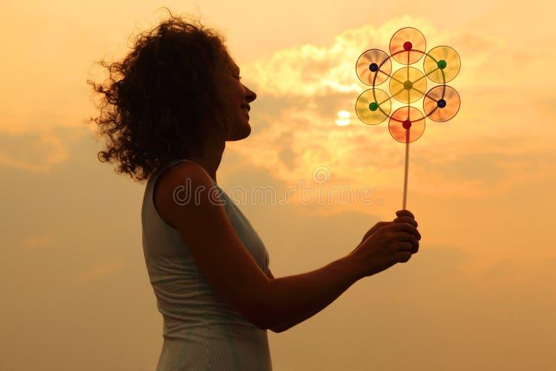 Whirligig do brinquedo da terra arrendada da mulher no por do sol fotografia de stock