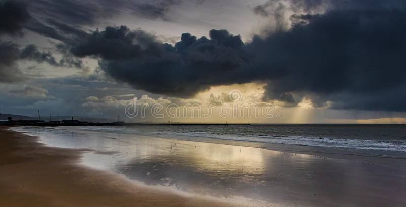 Whirling, black, solid storm clouds cover sun over a sea in Swan royalty free stock photography