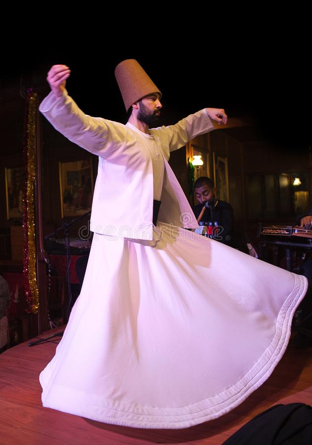 Whirling Dervish dance in Istanbul, Turkey. ISTANBUL, TURKEY - JANUARY 13, 2018: Whirling Dervish dance. It is called Sema and is a part of the inspiration of stock photography