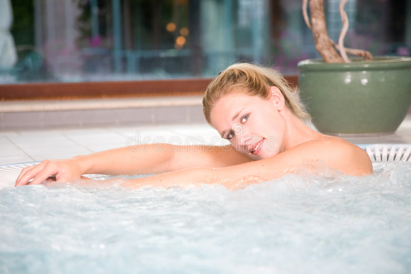 Whirlpool. Beautiful blond woman relaxing in the whirlpool at the beauty centre stock image