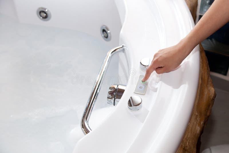 Whirlpool bath. White whirlpool bath with rock ready to take a bath stock image