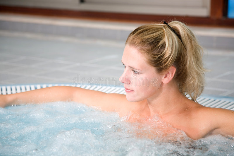 Whirlpool relaxation. Beautiful blond woman relaxing in the whirlpool stock photography