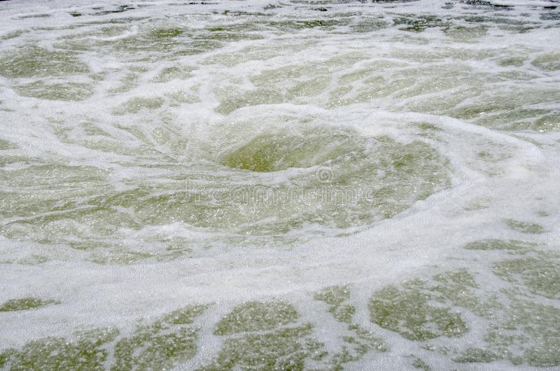 Whirlpool. A vortex whirlpool in frothy water stock photo