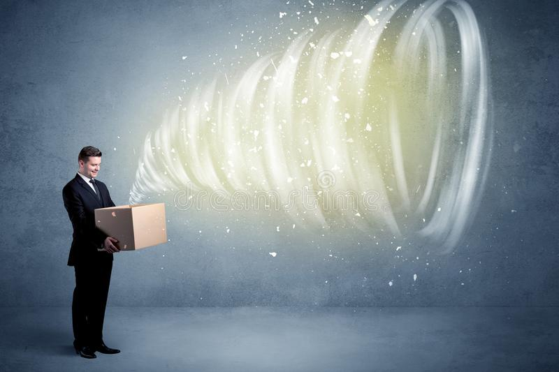 Whirlwind in box concept. An illustrated powerful whirlwind escaping, coming out of empty paper box held by elegant businessman concept royalty free stock image
