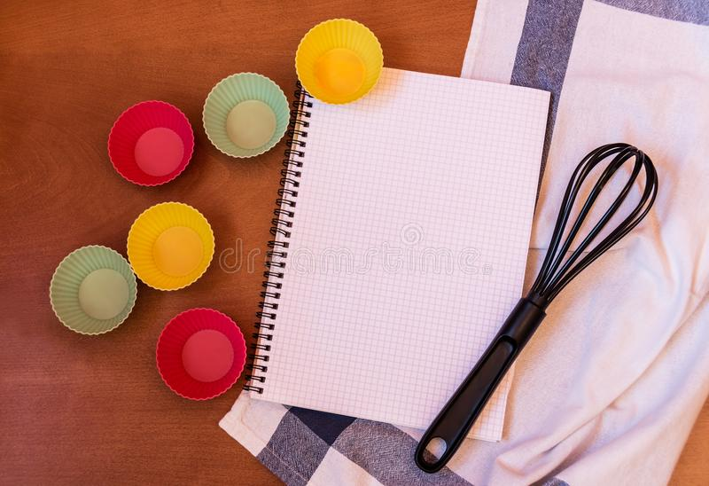 Whisk, cupcake silicon baking cups and empty notebook. On wooden background royalty free stock images