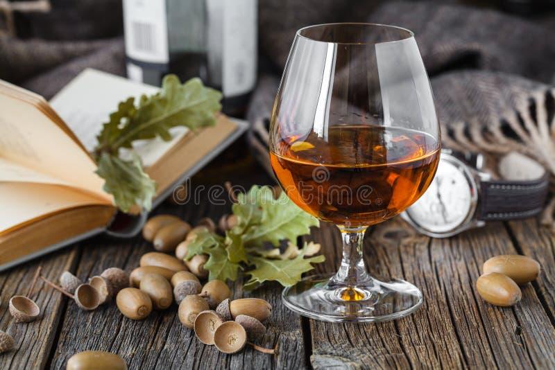Whiskey ambre de couleur d'oа en verre en verre sur la table de chêne photo stock