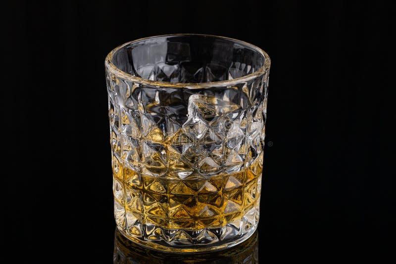 Whiskey avec de la glace dans les roches en verre sur le fond noir image stock