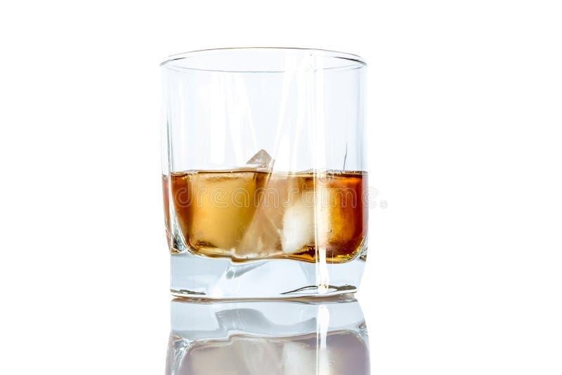 Whiskey avec le plan rapproché de glace dans un verre d'isolement sur un fond blanc photo stock