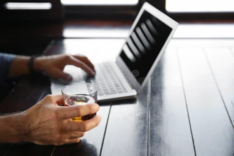Whiskey bevente dell'uomo senior mentre lavorando al computer portatile in pub, primo piano immagini stock libere da diritti