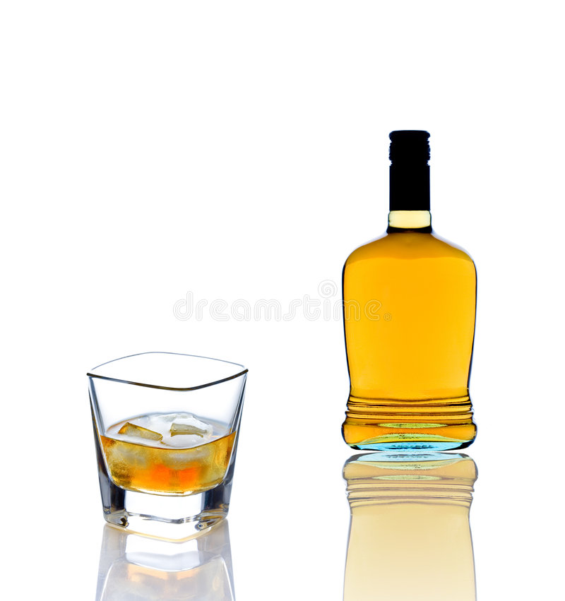 Whiskey bottle and a whiskey glass royalty free stock image