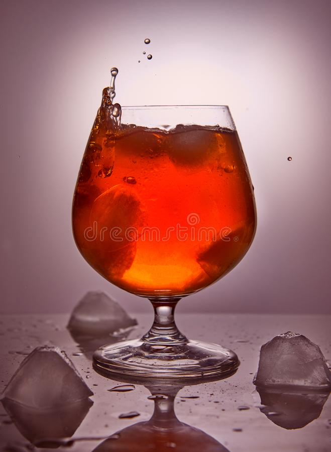 Whiskey, bourbon, brandy or cognac with ice on a pink background royalty free stock image