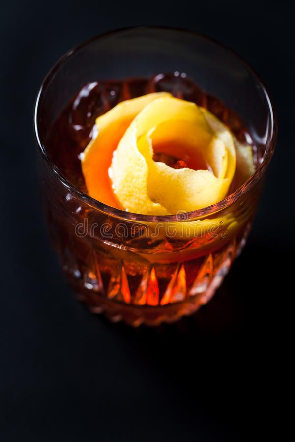Whiskey and campari cocktail garnished with orange peel. On dark background stock images