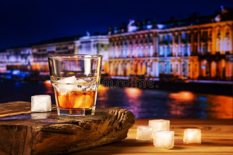 Whiskey cocktail with ice on wooden table stock photo