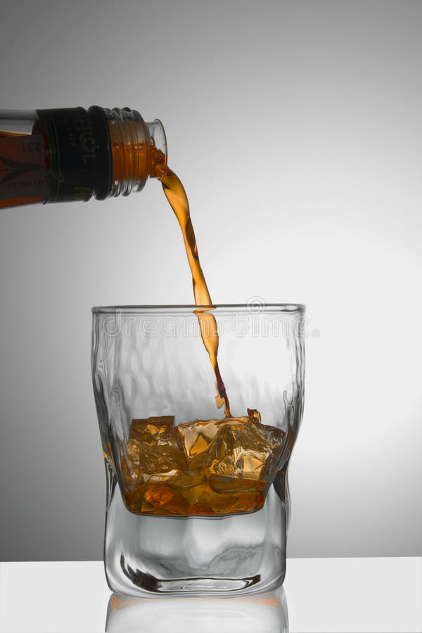 Whiskey/Cognac Being Poured Into A Glass Royalty Free Stock Photos