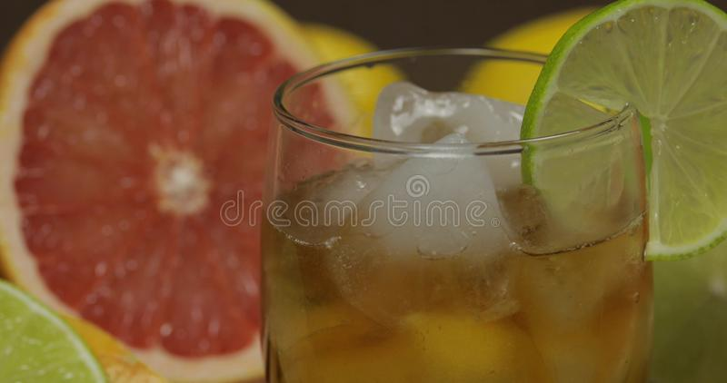 Whiskey, cognac, liqueur in a glass cup. Close-up. Liquor in a glass cup with ice cubes. Close-up shot. Fresh fruits in the background. Lime Grapefruit. Prepare stock photo