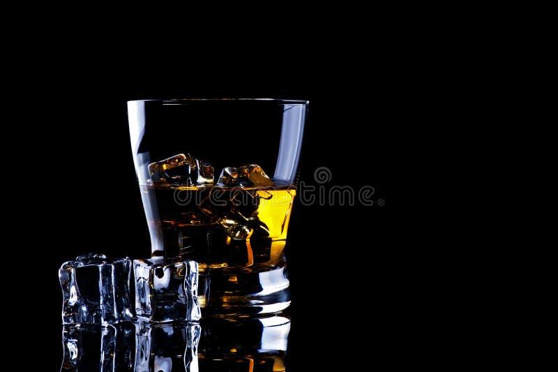 Whiskey con il cubetto di ghiaccio su backgroung nero immagini stock libere da diritti